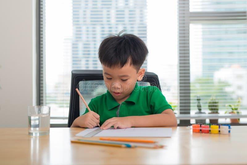 Netter Junge zeichnet mit den Farbbleistiften, lokalisiert über Weiß lizenzfreie stockfotografie