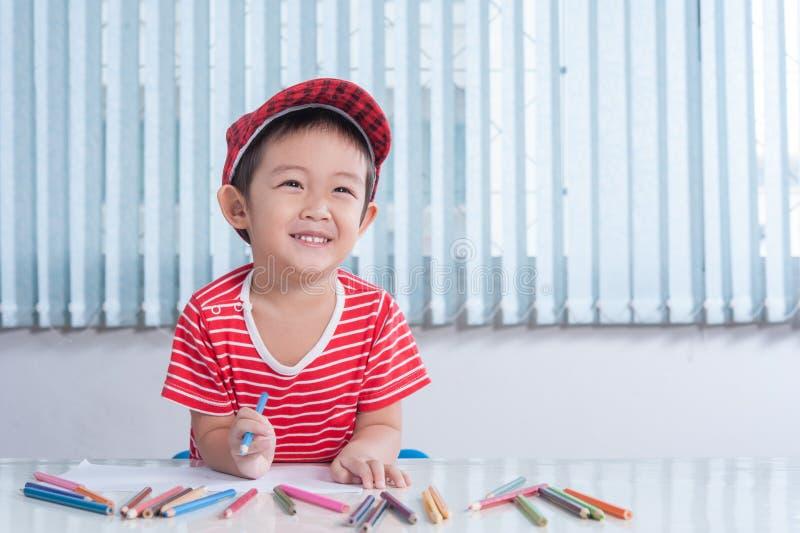 Netter Junge zeichnet mit Farbbleistiften im children& x27; s-Raum lizenzfreies stockfoto