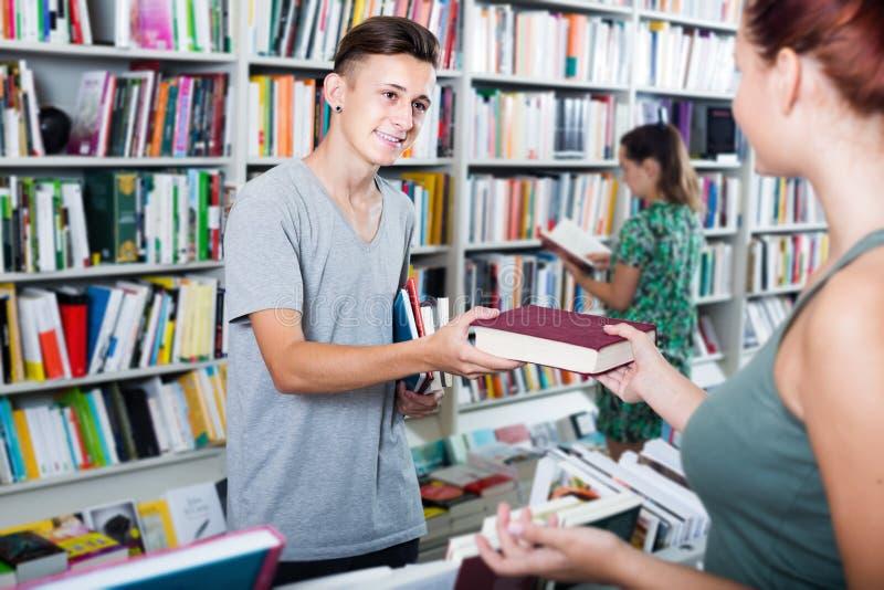 Netter Jungenjugendlicher, der neues Buch vom Verkäufer nimmt lizenzfreies stockbild