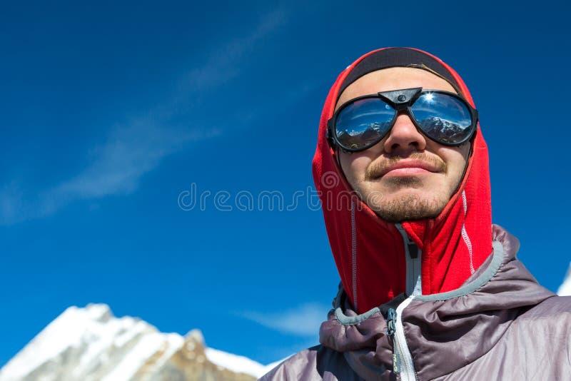 Netter junger Bergsteiger in der Sonnenbrille und in der Schutzkleidung lizenzfreie stockfotografie