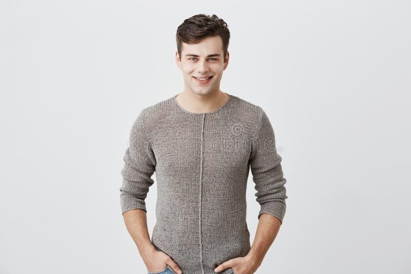 Netter junger blauäugiger Mann mit dem dunklen Haar, das im Studio mit glücklichem Lächeln, hübscher Sitzmann aufwirft, kleidete  stockbilder