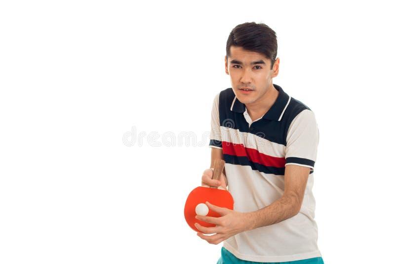 Netter junger Brunettemann in übendem Tischtennis der Uniform lokalisiert auf weißem Hintergrund stockfoto
