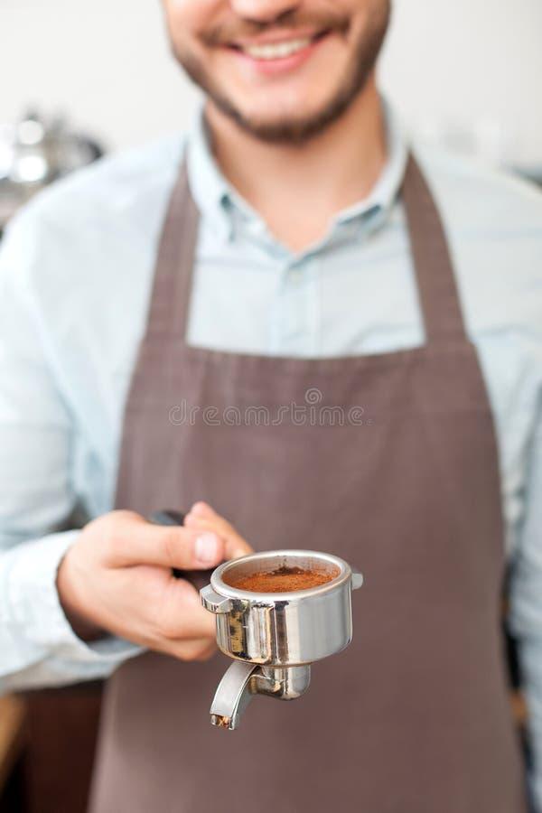 Netter junger Caféinhaber arbeitet mit Freude lizenzfreie stockbilder