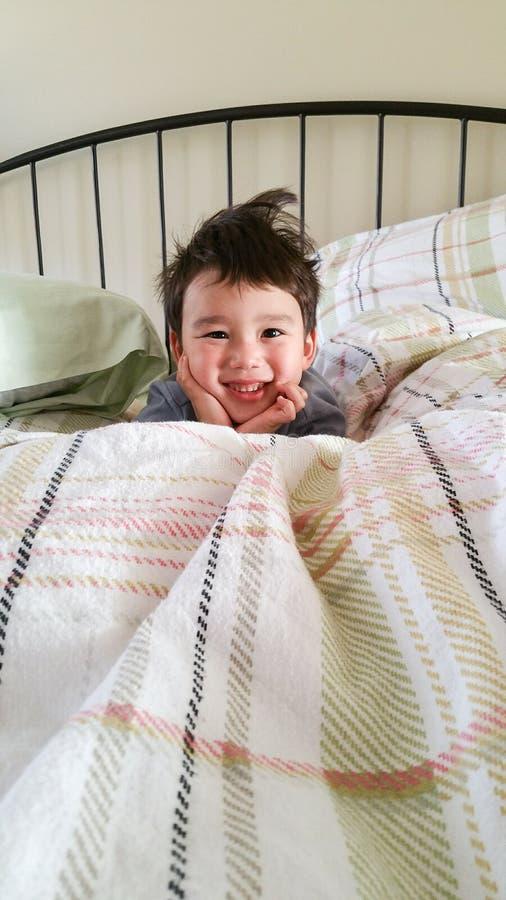 Netter junger chinesischer und kaukasischer Junge, der auf Bett aufwacht lizenzfreie stockfotos