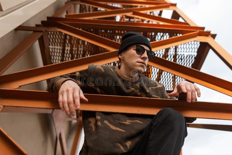 Netter junger Hippie-Mann in der Strickmütze im Tarnungshemd in der Sonnenbrille, die draußen Sitzen auf einem orange Treppenhaus lizenzfreie stockfotografie