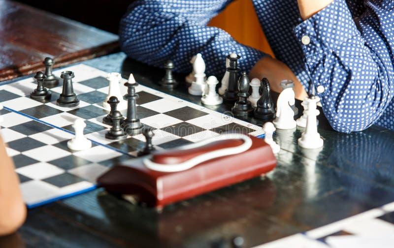 Netter junger intelligenter Junge im blauen Hemd spielt Schach auf dem Training vor dem Turnier Schachsommerlager liebhaberei stockfotografie