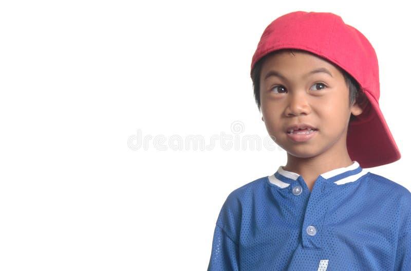 Netter junger Junge in der roten Baseballmütze stockfotografie
