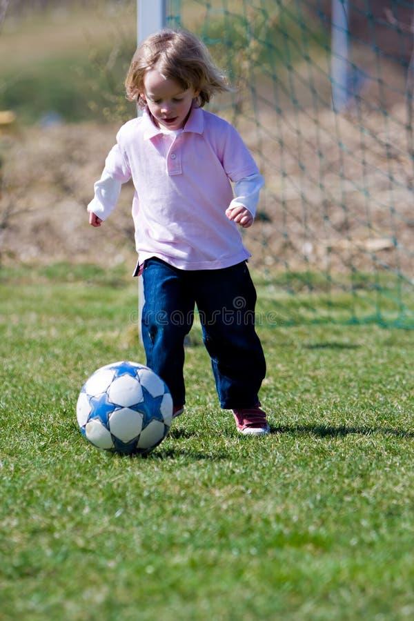 Netter junger kaukasischer Junge, der Fußball spielt lizenzfreies stockbild