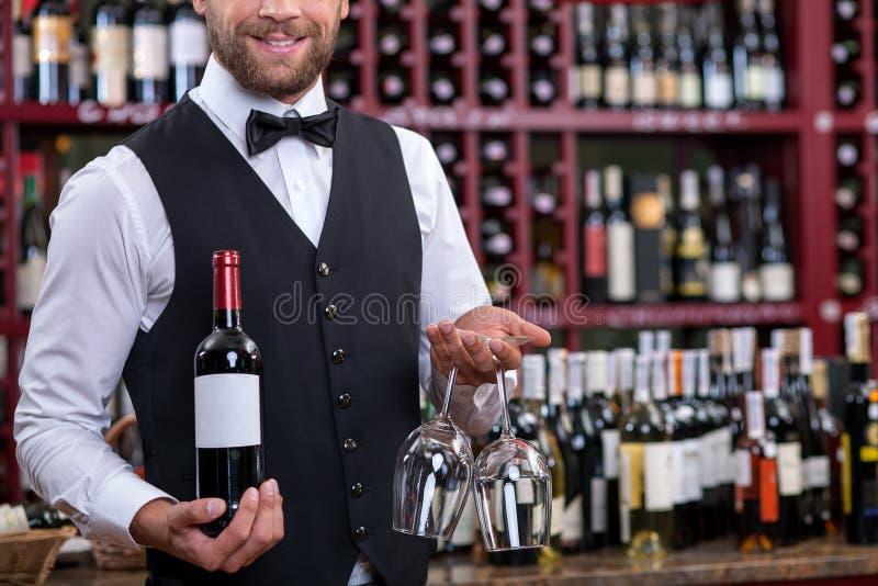 Netter junger Kellner trägt Alkoholgetränk herein stockfoto