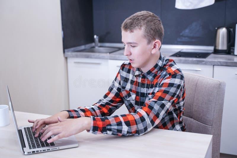 Netter junger Kerl, der in einem karierten Hemd mit einem Laptop und einem Arbeiten, zu Hause studierend allein sitzt stockfoto