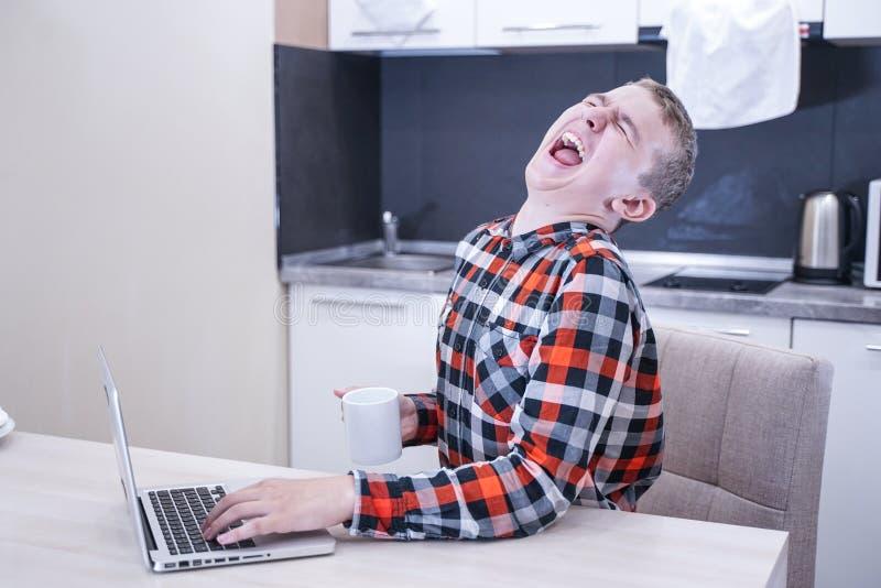 Netter junger Kerl, der in einem karierten Hemd mit einem Laptop und einem Arbeiten, zu Hause studierend allein sitzt stockbilder