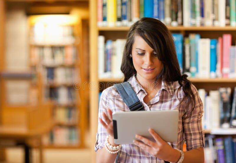 Netter junger Kursteilnehmer, der einen Tablettecomputer verwendet lizenzfreie stockbilder