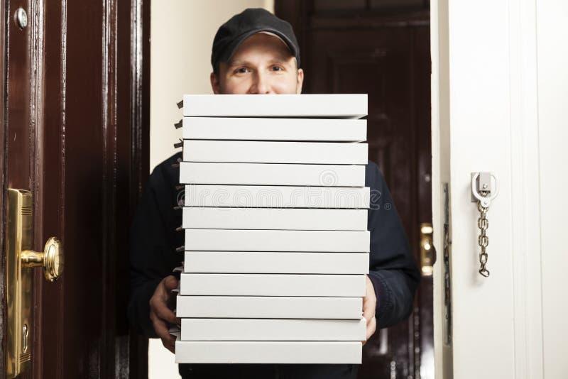 Netter junger Lieferbote, der einen Pizzakasten hält, während Sie auf Weiß lokalisiert werden lizenzfreie stockfotografie