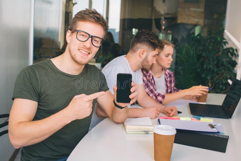 Netter junger Mann in den Gläsern zeigen auf hpone in den Händen Er schaut auf Kamera Andere zwei junge Leute arbeiten bei einem  stockbild