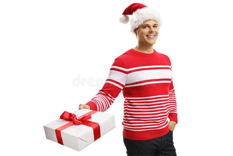 Netter junger Mann, der einen Weihnachtsmann-Hut trägt und ein Geschenk hält stockbild