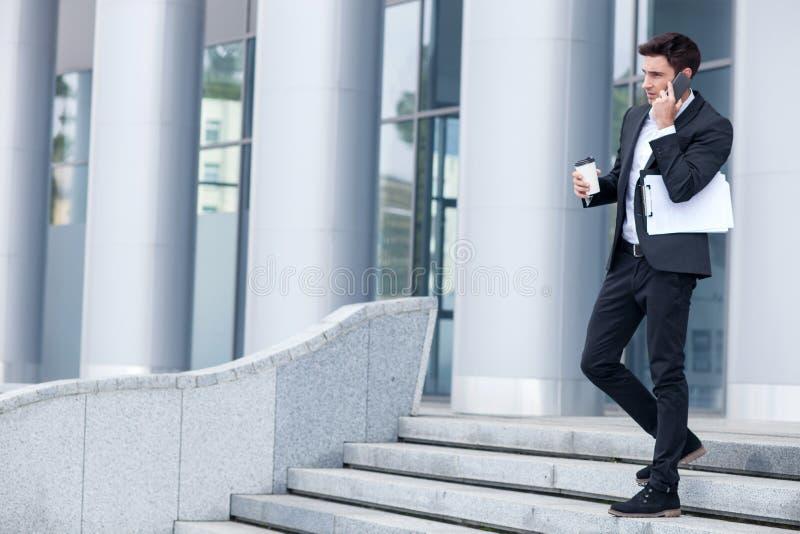 Netter junger Mann in der Klage benutzt Telefon stockbild