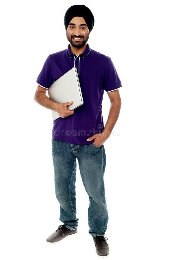 Netter junger Mann, der Laptop hält stockfotografie
