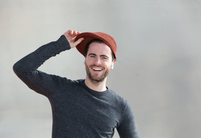 Netter junger Mann, der mit Hut lacht lizenzfreie stockfotos