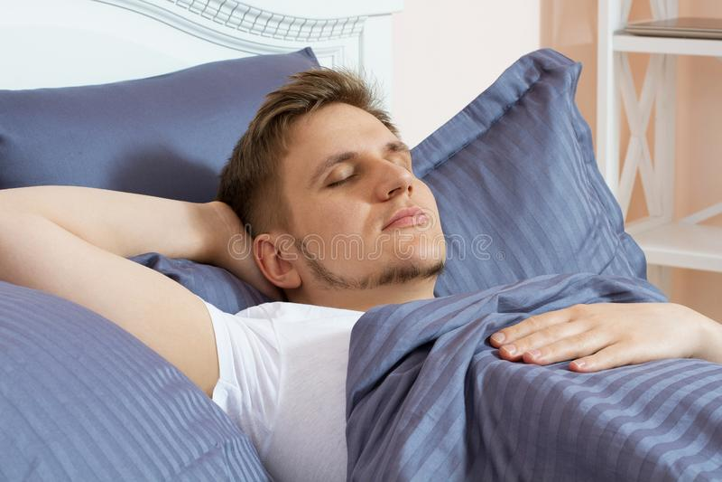 Netter junger Mann, der morgens auf Bett schläft stockfoto