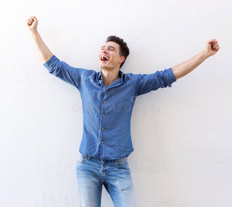 Netter junger Mann mit den angehobenen Armen feiernd stockfoto