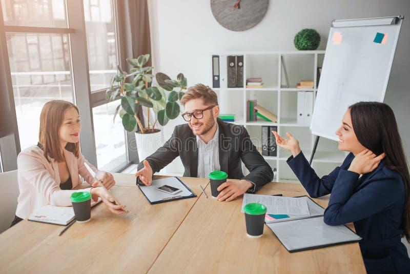 Netter junger Mann und Frauen sitzen zusammen bei Tisch in Konferenzzimmer Sie haben Gespräch und Lachen Leutearbeit und -gespräc stockfotos