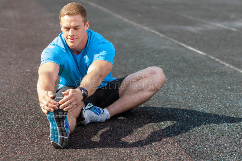 Netter junger Mann wärmt auf, bevor er läuft stockfotografie