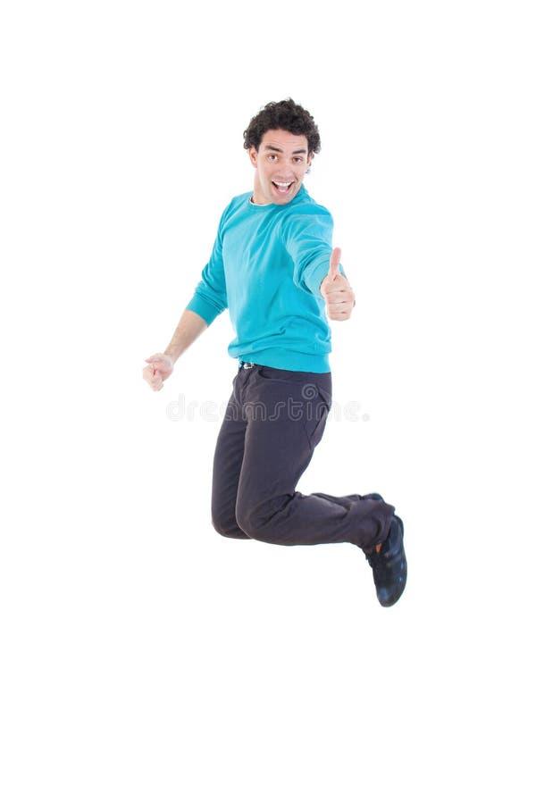 Netter junger zufälliger Mann, der in einer Luft sich zeigt Daumen springt lizenzfreie stockfotografie