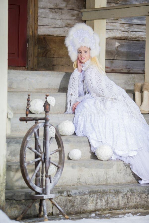 Netter Kaukasier blond in gestricktem weißem Kleid und in Halstuch mit Pelz Kokoshnik Aufstellung vor altem Holzhaus mit Spindel stockfotos