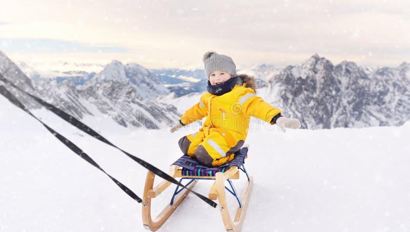Netter kaukasischer kleiner Junge, der in den Alpenbergen rodelt stockbild