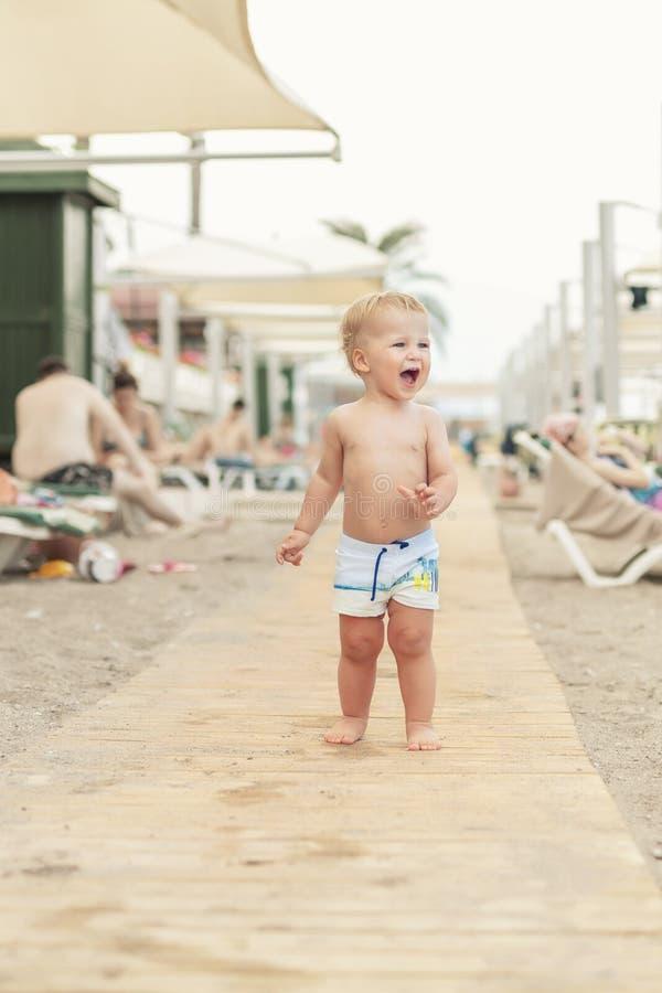 Netter kaukasischer toodler Junge, der allein auf sandigen Strand zwischen Wagenaufenthaltsraum geht Entzückendes glückliches Kin stockfotografie