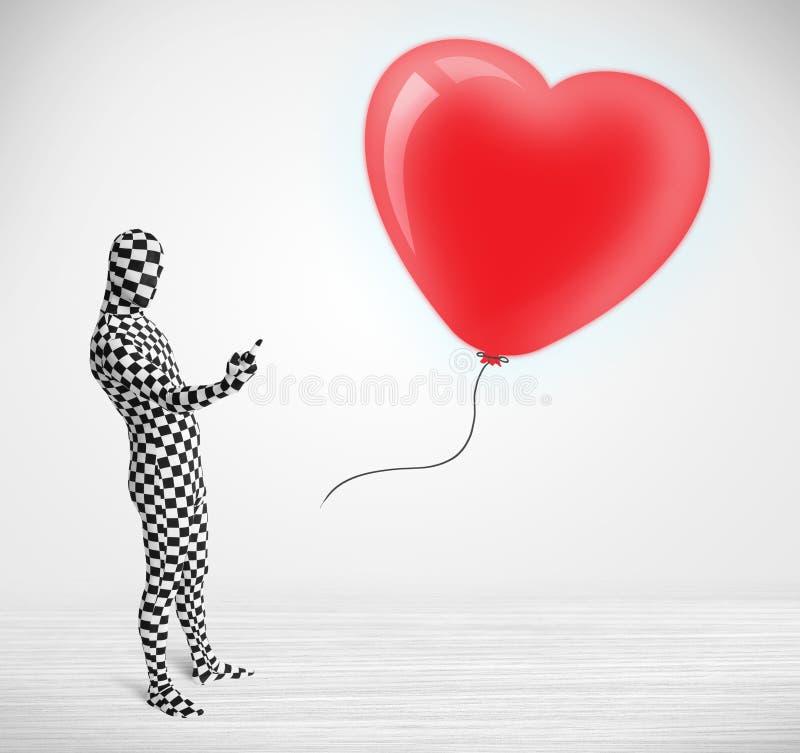 Netter Kerl in der morpsuit Körperklage, die einen Ballon betrachtet, formte Herz stockfotos