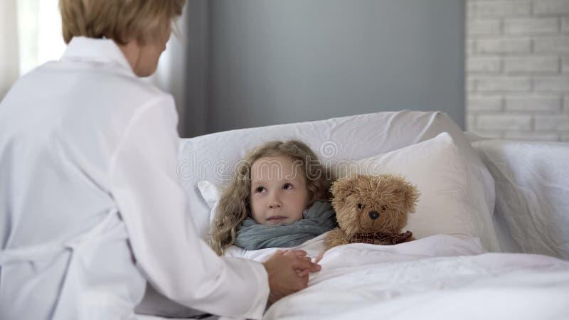 Netter Kinderarzt, der zu Hause krankes kleines M?dchen, Doktor tr?stet krankes Kind ?berpr?ft stockfotografie