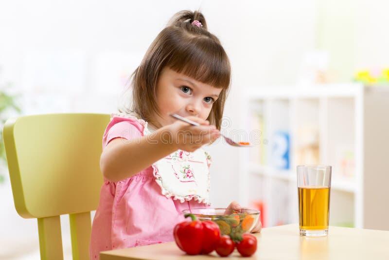 Netter Kinderjunge isst gesundes Lebensmittelgemüse stockfotografie