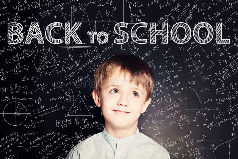 Netter Kinderschuljunge auf Tafel-Hintergrund stockfoto