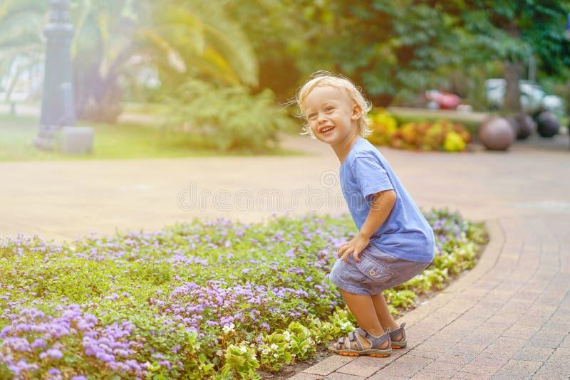 Netter kleiner blonder Junge, der im Parklächeln spielt stockbilder