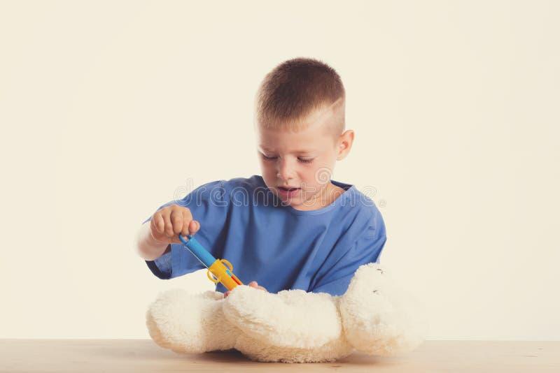 Netter kleiner Doktorjunge mit Lächeln auf dem Gesicht, das an seinem Schreibtisch auf weißem Hintergrund sitzt Intelligente Kind lizenzfreies stockbild