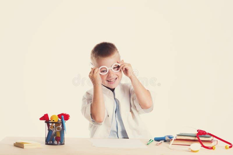 Netter kleiner Doktorjunge mit Lächeln auf dem Gesicht, das an seinem Schreibtisch auf weißem Hintergrund sitzt Intelligente Kind lizenzfreie stockfotos