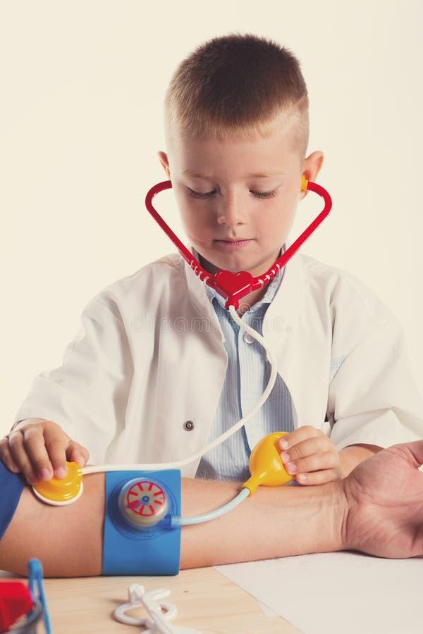 Netter kleiner Doktorjunge mit Lächeln auf dem Gesicht, das an seinem Schreibtisch auf weißem Hintergrund sitzt Intelligente Kind stockfotografie