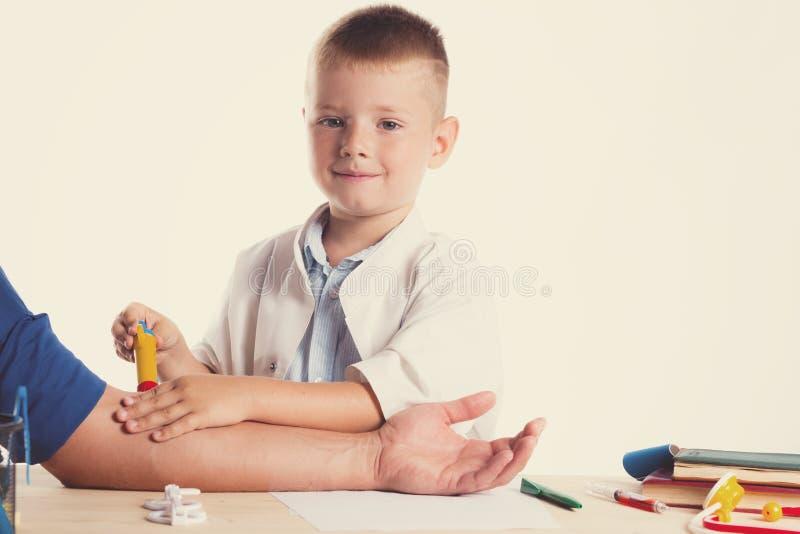 Netter kleiner Doktorjunge mit Lächeln auf dem Gesicht, das an seinem Schreibtisch auf weißem Hintergrund sitzt Intelligente Kind lizenzfreie stockbilder