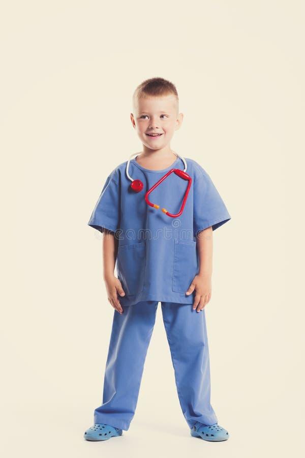 Netter kleiner Doktorjunge mit Lächeln auf Gesicht auf weißem Hintergrund Intelligente Kinder in Doktorklage mit blauen Augen und stockfotos