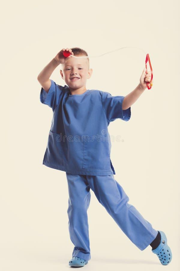 Netter kleiner Doktorjunge mit Lächeln auf Gesicht auf weißem Hintergrund Intelligente Kinder in Doktorklage mit blauen Augen und stockfotografie