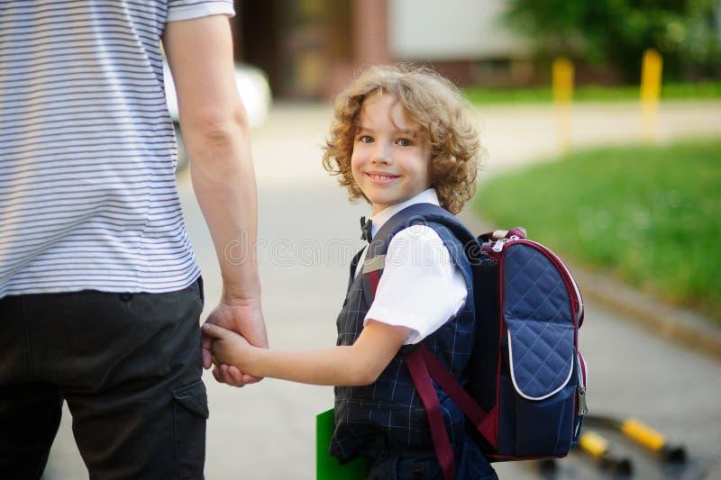 Netter kleiner erster Sortiererstudent, der zur Schule mit Vati geht stockfotos
