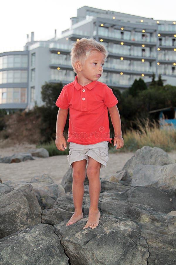Netter kleiner Junge auf den Felsen lizenzfreie stockfotografie