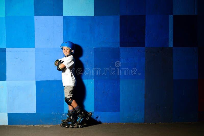 Netter kleiner Junge auf den Rollschuhen, die gegen die blaue Graffitiwand stehen stockbild