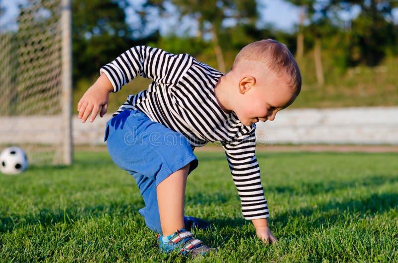 Netter kleiner Junge auf einem Fußballplatz stockbild