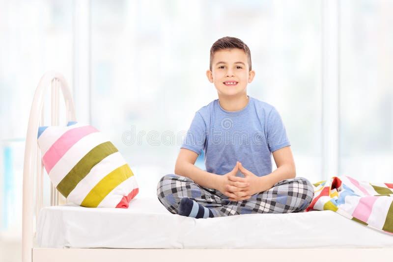 Netter kleiner Junge in den Pyjamas, die auf einem Bett sitzen lizenzfreies stockbild
