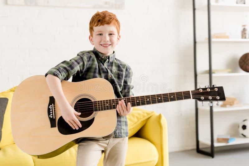 netter kleiner Junge, der Akustikgitarre und das Lächeln hält stockfoto