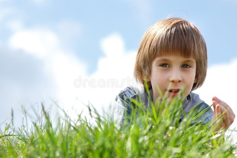 Netter kleiner Junge, der auf die Frühlingsnatur des grünen Grases im Freien legt stockfotos