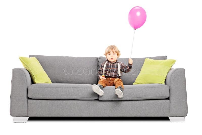 Netter kleiner Junge, der auf Sofa mit einem Heißluftballon sitzt stockfoto