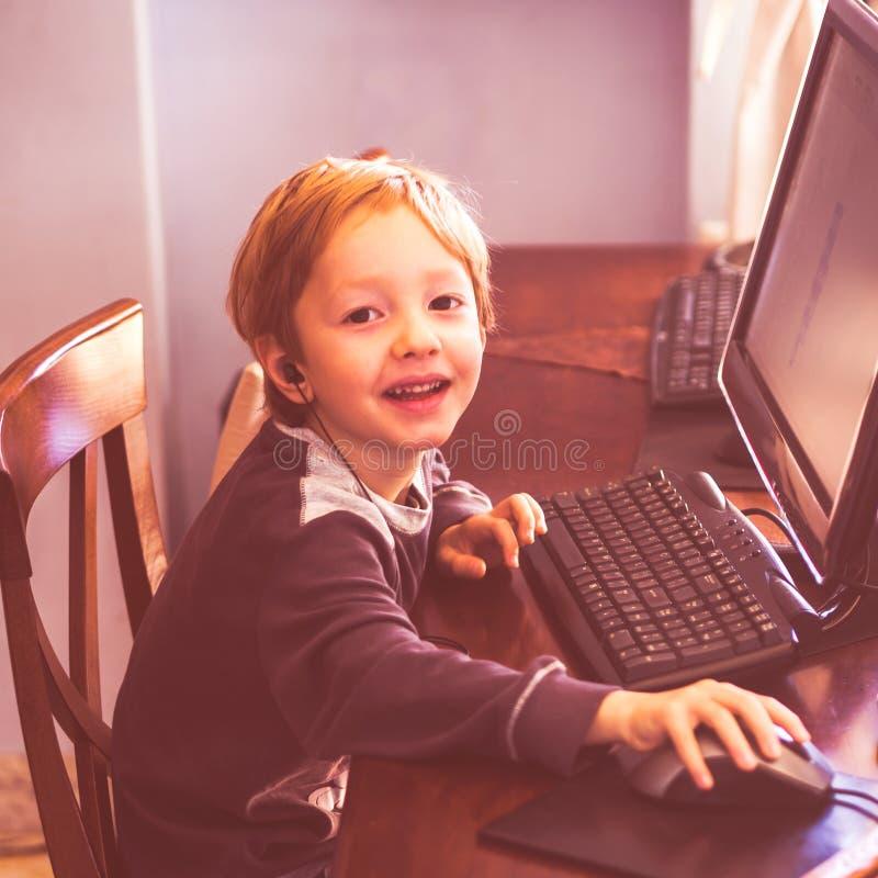 Netter kleiner Junge, der am Computer mit Kopfhörer spielt lizenzfreie stockfotos